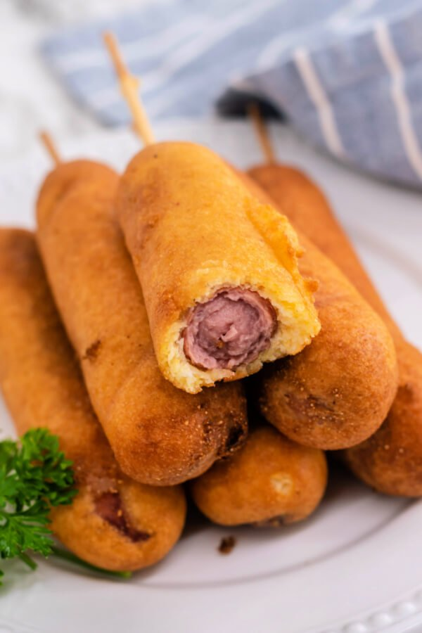 corn dogs stacked on plate with a bite taken out of the top one