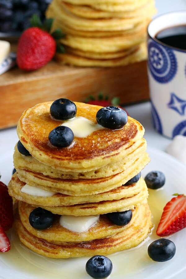 stack of cornbread pancakes with blueberries and syrup