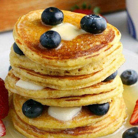 closeup of stack of Cornmeal Pancakes with blueberries and maple syrup