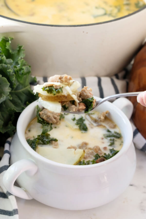 spoonful of Zuppa Toscana soup over bowl