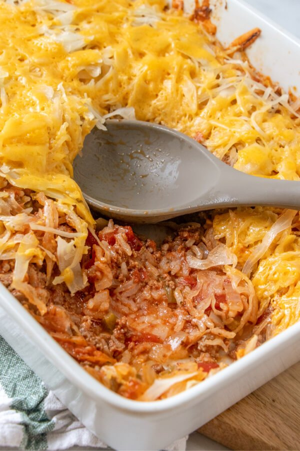 unstuffed cabbage roll casserole in baking dish with a scoop of the finished dish removed