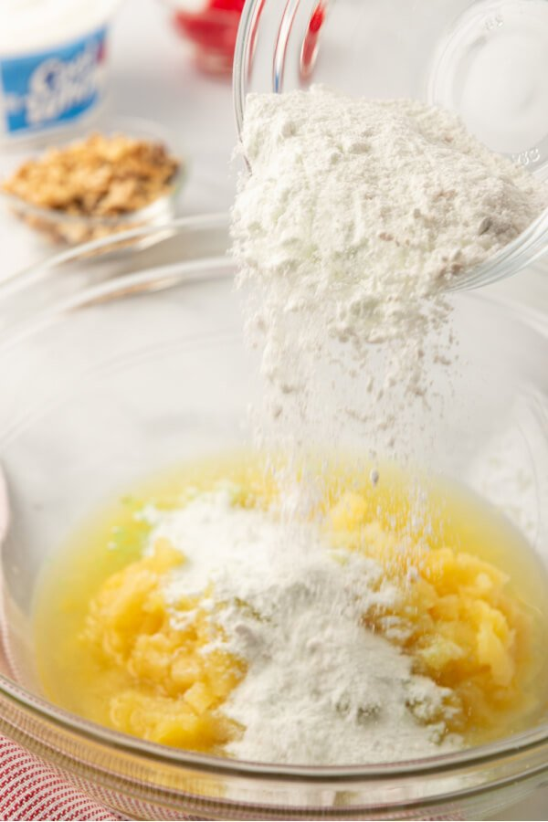 pudding mix being poured into crushed pineapple in bowl
