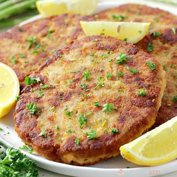 Salmon Patties on a white plate garnished with lemon and parsley