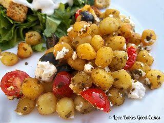 Crispy Pesto Gnocchi with Tomatoes, Black Olives and Feta Cheese with green salad on white plate