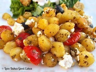 Crispy Pesto Gnocchi with Tomatoes, Black Olives and Feta Cheese with green salad on white plate close up