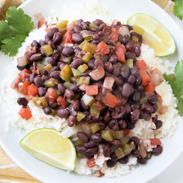 cuban black beans and rice on white plate with lime wedges