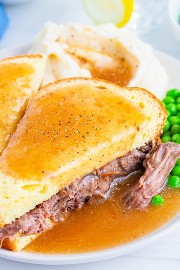 hot roast beef sandwich with gravy on plate with pashed potatoes and gravy and peas