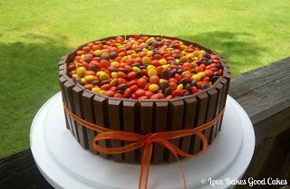 Kit-Kat Cake with reeses pieces on top and orange bow on white cake stand