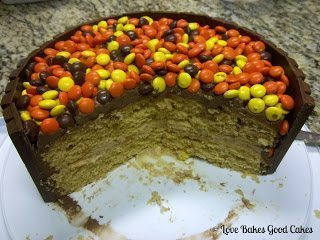 Kit-Kat Cake with reeses pieces on top with slice removed on white cake stand
