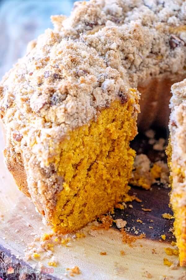 Pumpkin Streusel Coffee Cake on cake stand with piece removed