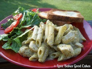Creamy Chicken and Pesto Pasta with green salad and tomatoes and toast on red plate