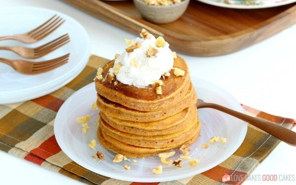 Pumpkin pancakes stacked up on a plate with a fork.