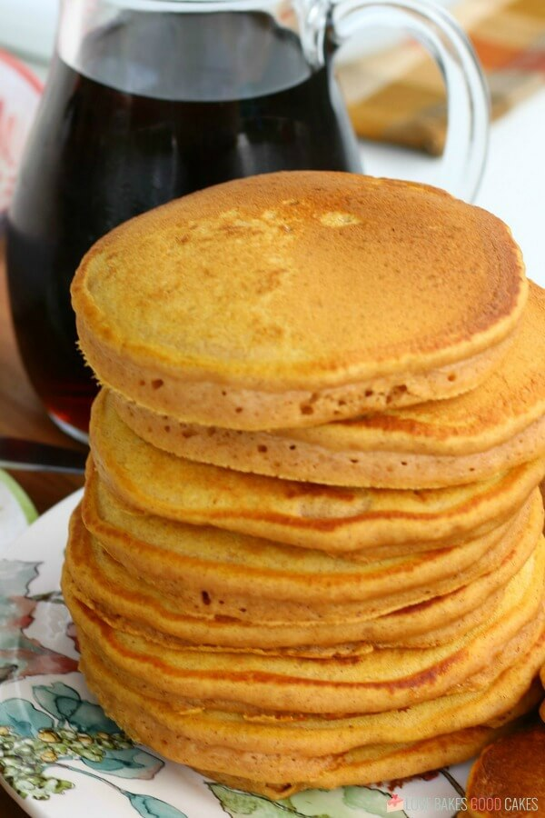 Pumpkin pancakes stacked up on a plate with a bottle of syrup