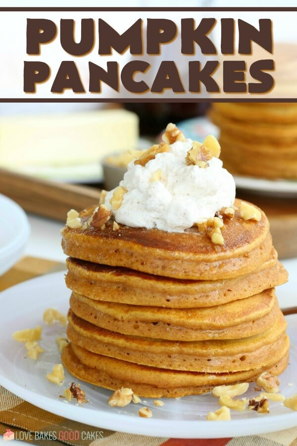 Pumpkin pancakes stacked up on a plate with nuts and whipped cream on top.