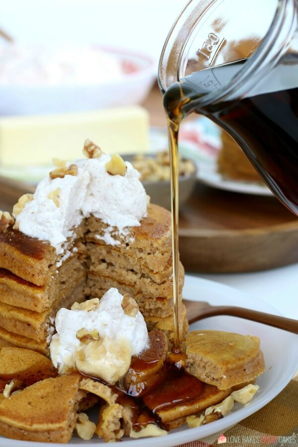 Pumpkin pancakes stacked up on a plate with syrup being poured over the top.