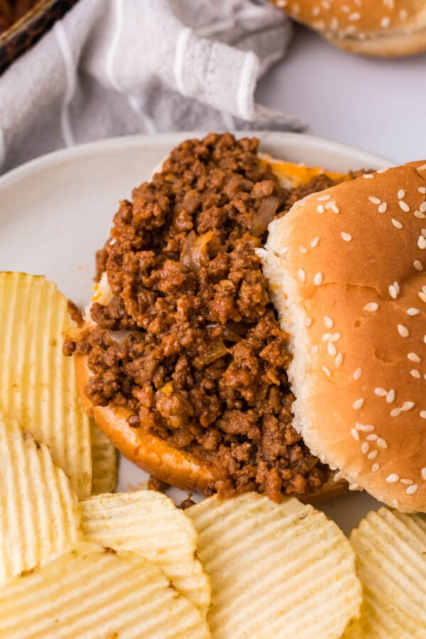 sloppy joes sauce with meat filling on bun and partially covered by the top bun