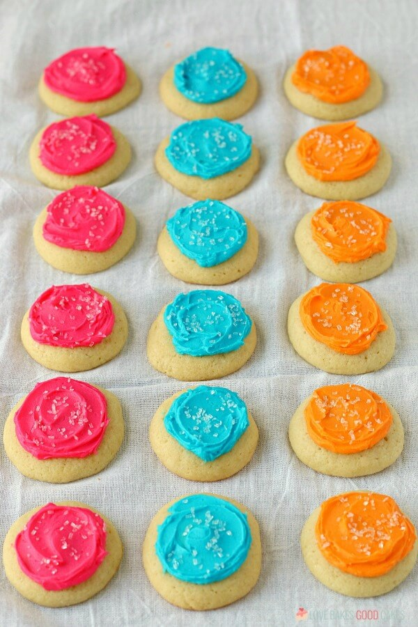 Soft Sugar Cookies laying on a cloth in different colors.