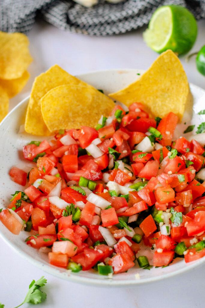 pico de gallo in bowl with a couple of tortilla chips