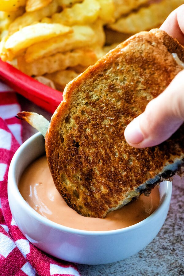 dunking patty melt sandwich into sauce