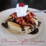 Banana Split Pancakes stacked on plate with whipped cream, strawberries and chocolate syrup.