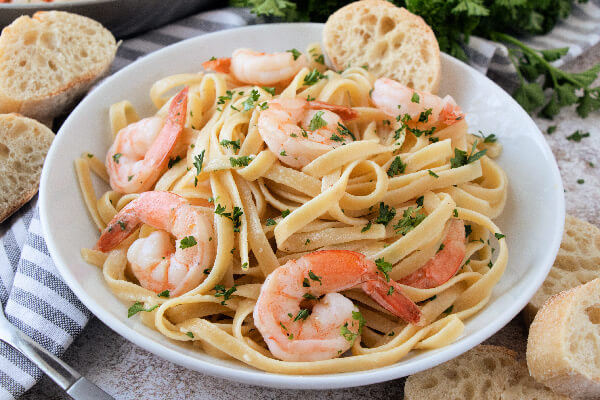 shrimp scampi pasta in white bowl with a slice of bread