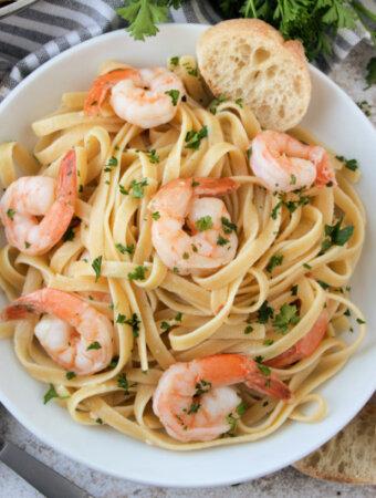 closeup of shrimp scampi pasta in white bowl