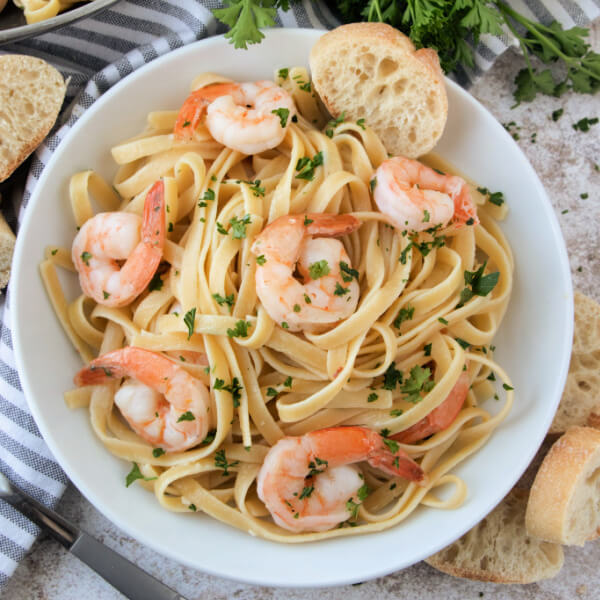 closeup of shrimp scampi pasta in white bowl