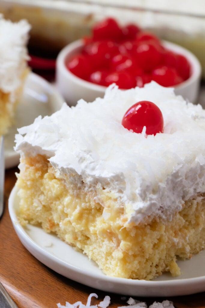 pina colada poke cake slice on white plate
