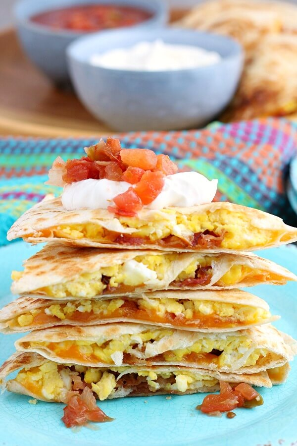 This stack of egg quesadillas is finished and ready to be eaten, topped with sour cream and salsa.