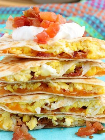 A close up view of the finished breakfast quesadillas recipe with salsa and sour cream ready to be shared!