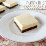 Pumpkin Spice Cheesecake Bar on plate with bars in the background.