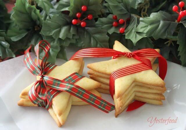 Cornmeal Stars with Orange Glaze stacked and wrapped with ribbons on plate.