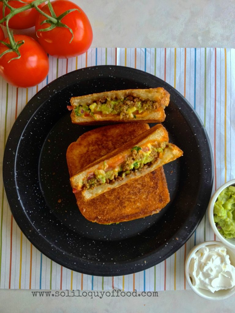 Layers of cheddar cheese, taco meat, guacamole, sliced tomatoes, and Monterrey Jack cheese - Taco Stuffed Grilled Cheese - www.soliloquyoffood.com