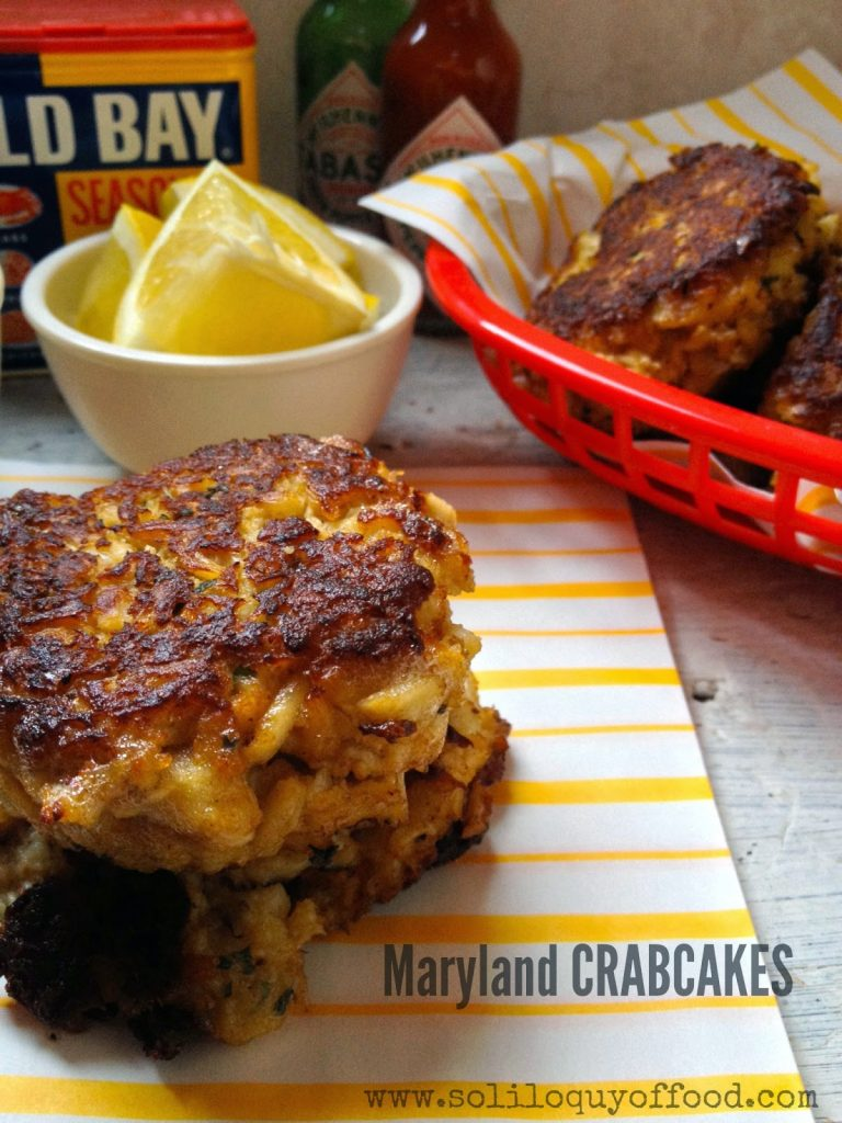 Maryland Crab Cakes in basket and on plate with lemon wedges.