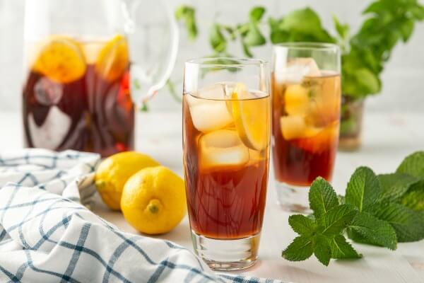 two glasses of sweet tea with pitcher of tea in background
