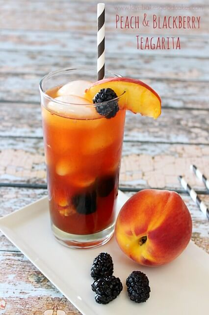 Jose Cuervo Iced Teagarita consists of the classic limeA Peach and Blackberry Teagarita in a glass with a peach next to the glass.