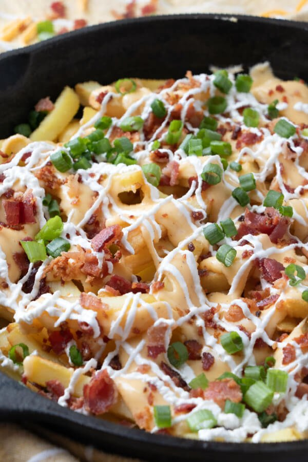 closeup of cheese fries with bacon in cast iron skillet