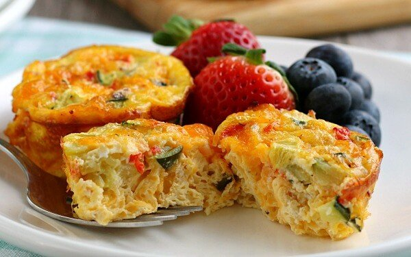 muffin tin egg split in half on plate with berries