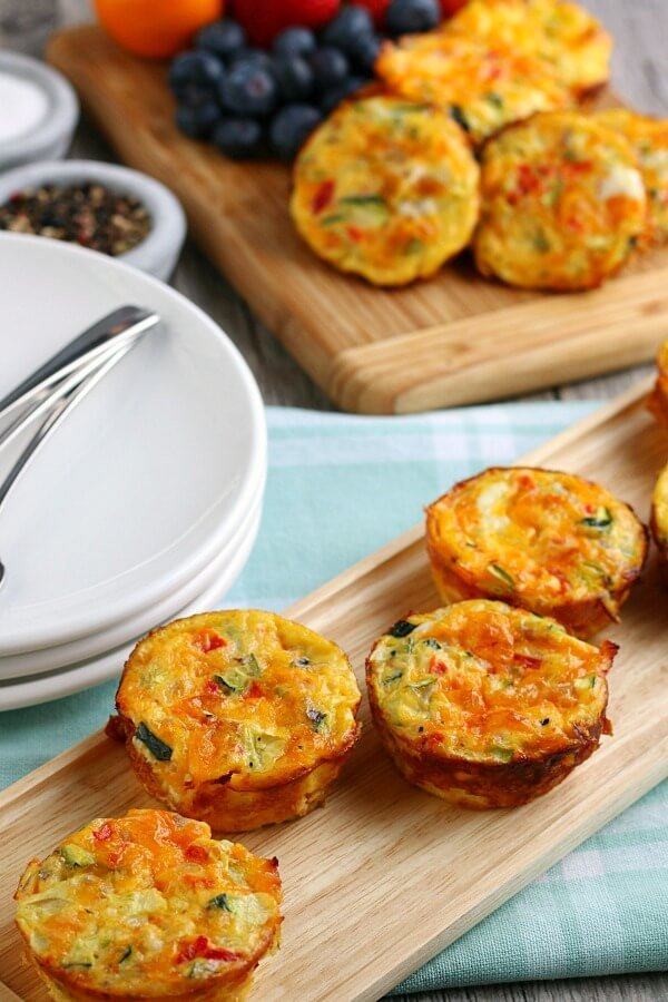 breakfast egg muffins in foreground on cutting board, breakfast table setting in background
