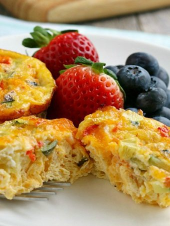 closeup of breakfast egg muffin on plate with fruit