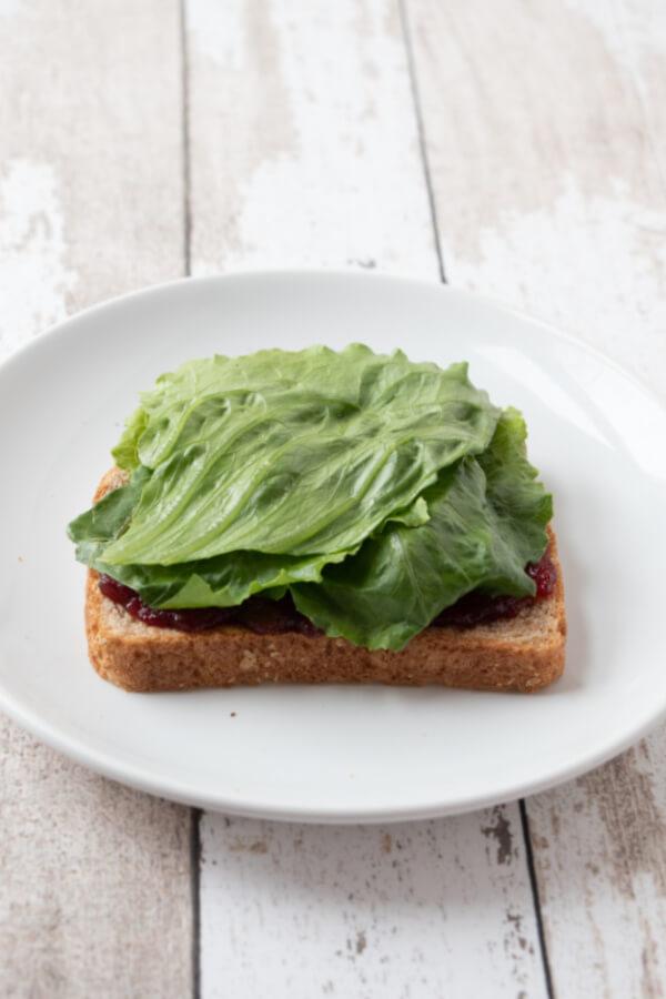 adding lettuce to sandwich