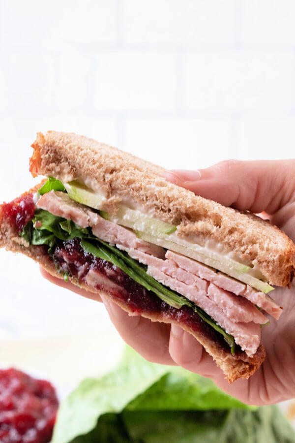 hand holding sandwich half