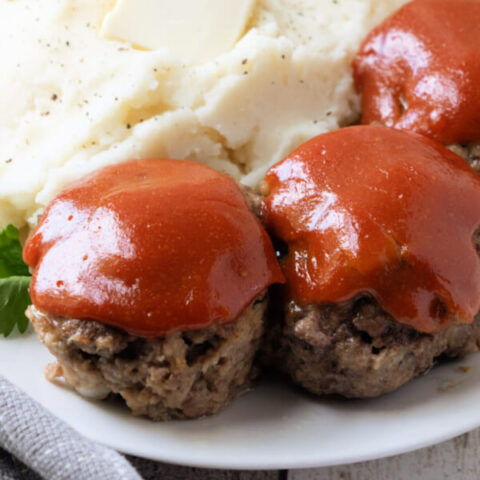 three meatloaf muffins lined up on a plate with mashed potatoes