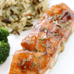 Dr Pepper Glazed Salmon on a white plate with rice pilaf.