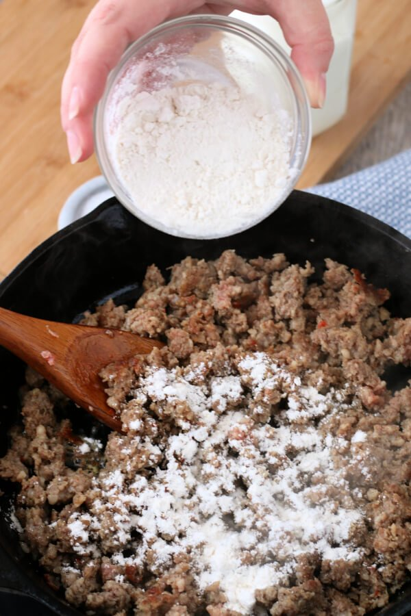 adding flour to the browned and crumbled sausage