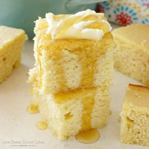 Southern Cornbread stacked up on a plate with butter and honey drizzle.