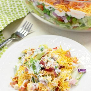 This 7 Layer Salad is the perfect addition to any meal or potluck. With layers of veggies, a tangy dressing, cheese, and bacon, this will be a new favorite!