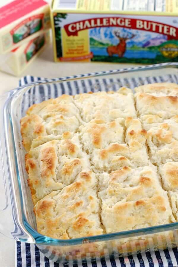 Butter Dip Biscuits sliced in a baking dish with Challenge Butter products.