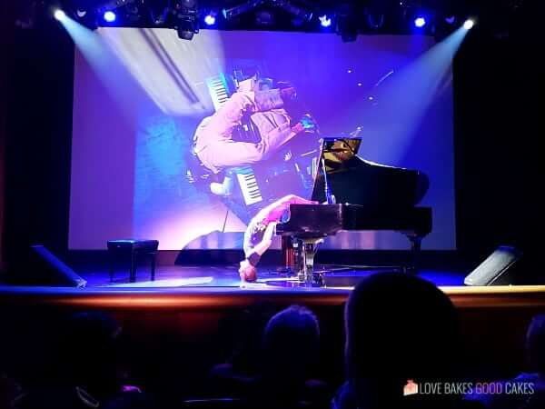 A man laying upside down on a piano while playing it on the stage of a cruise ship.