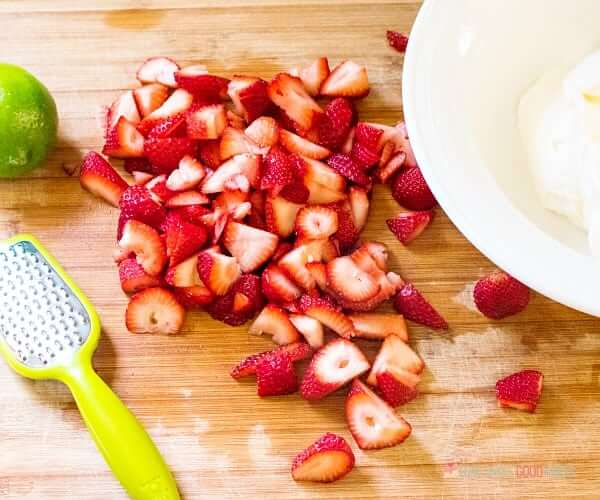 Strawberries sliced a cutting board.